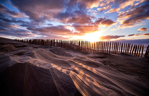 A stormy beach during sunset. The sky is filled with dark colored clouds and the sky is orange/yellow. There is a fence on the beach which is partially covered under sand that is blown in that direction.