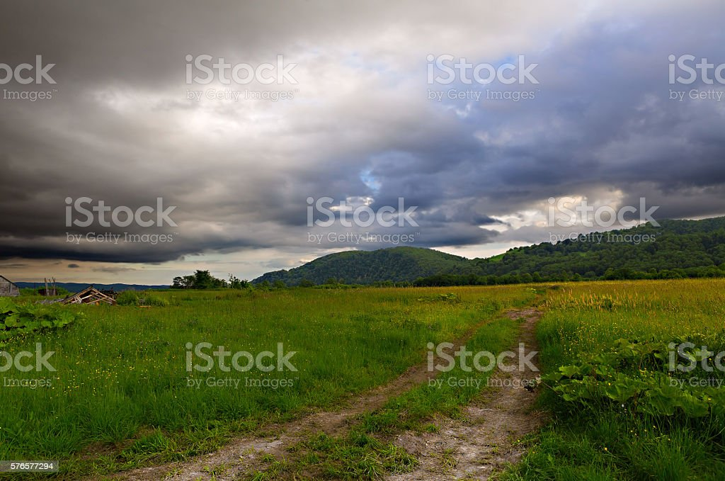 stormy cloud on meadow with rural road – Foto