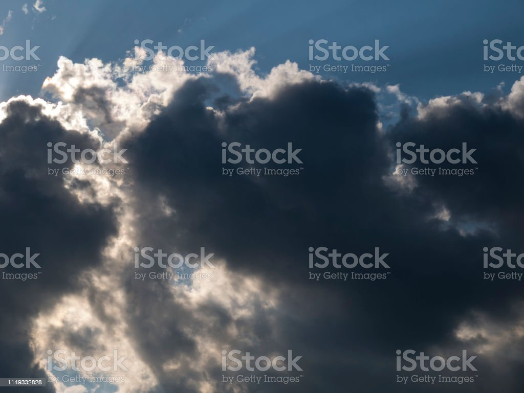 Stormy clouds with the sun, dramatic backdrop of the blue sky with...