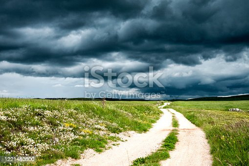 Dramatic stormy dark cloudy sky over field and footpath. Natural photo.