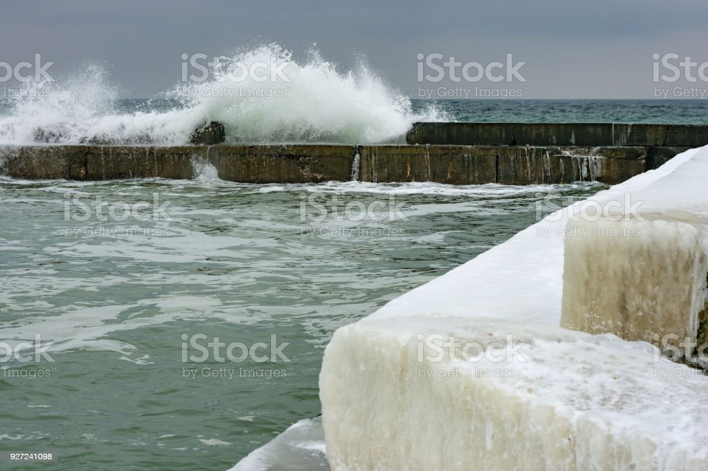Stormy day at winter beach. Icy waves breaking at snow covered rocks. stock photo