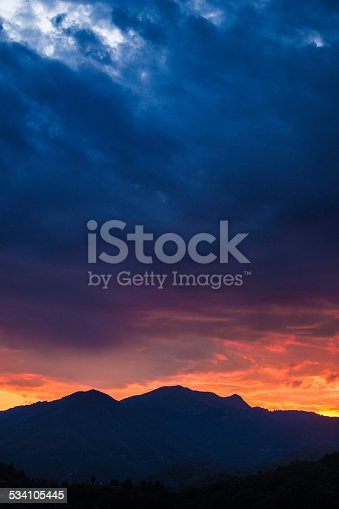 Storm clouds brewing over mountains during a sunset in Tuscany, Italy