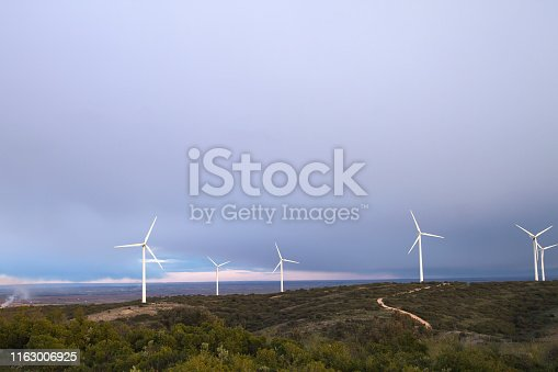 Landscape with wind turbines farm generating clean renewable energy in Spain, environmental concept