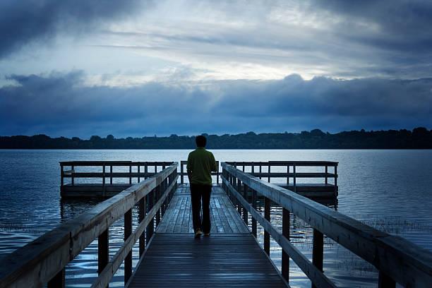 stürmischer tag mit einem mann zu fuß auf hölzernen dock auf see - boundary waters stock-fotos und bilder