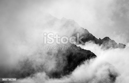 A mountain peak in the alps of Switzerland in black and white surrounded by clouds silhouetted against the rising sun.