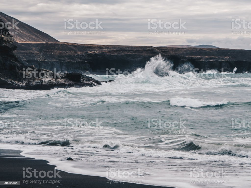 Stormachtige oceaan golven met witte schuim raken zwarte zand strand van Ajuy in Fuerteventura, Canarische eilanden, Spanje. Donkere wolken - Royalty-free Atlantische oceaan Stockfoto