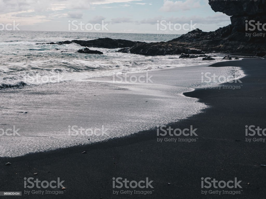 Stormy ocean waves with white foam hitting black sand beach of Ajuy in Fuerteventura, Canary Islands, Spain. Dark clouds - Royalty-free Atlantic Ocean Stock Photo