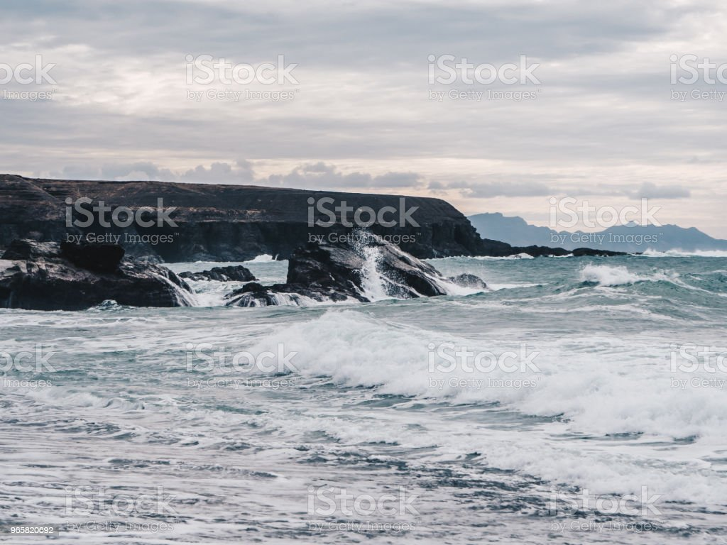 Stormy ocean waves with white foam hitting the cliffs and black sand beach of Ajuy in Fuerteventura, Canary Islands, Spain. Dark clouds - Royalty-free Atlantic Ocean Stock Photo