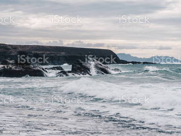 Stormy Ocean Waves With White Foam Hitting The Cliffs And Black Sand Beach Of Ajuy In Fuerteventura Canary Islands Spain Dark Clouds Stock Photo - Download Image Now
