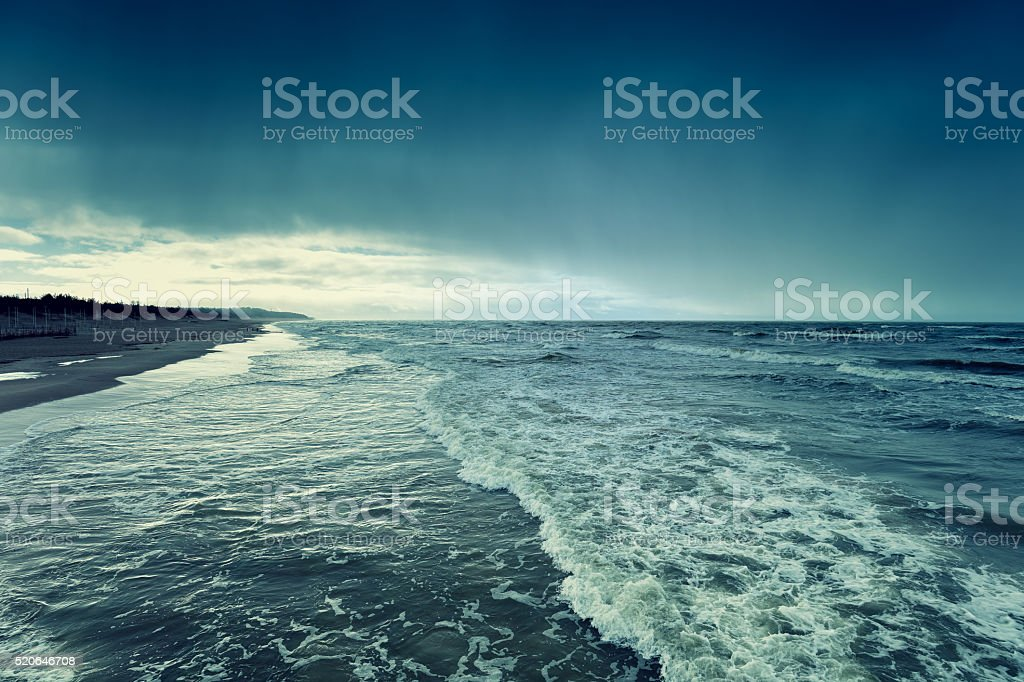 Stormy rainy weather on the deserted beach stock photo