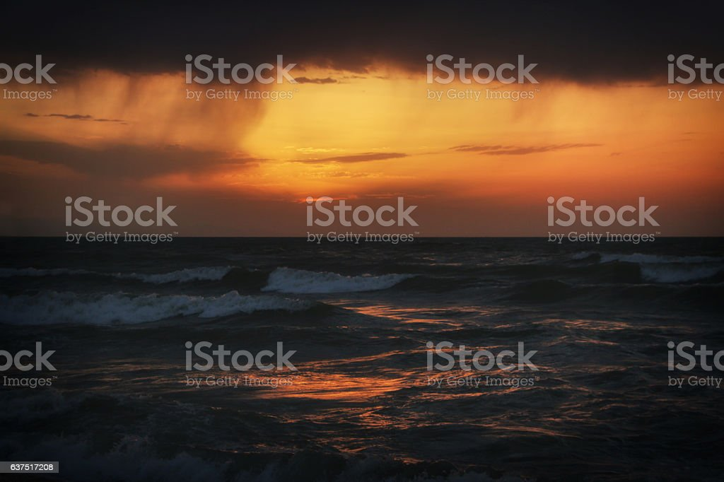 stormy sea at sunset stock photo