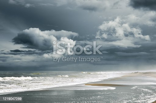 Stormy sea, beach and clouds at dark dramatic sky