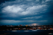 Urban lightening storm with rainy dark clouds on Bosphorus and Istanbul city in Turkey