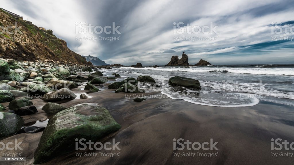 Stones on the beach of black volcanic sand after low tide on the...