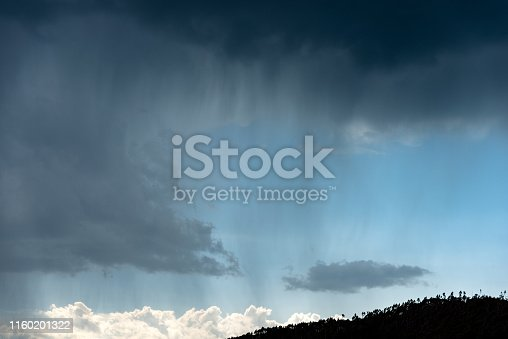 Stormy sky and rain over the pine forest, black silhouette. Italian Alps, Trentino Alto Adige, Italy, Europe