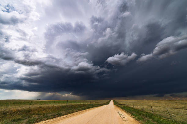 Stormy sky over a dirt road and field. stock photo