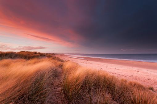 Stormy sunset over sand dunes and the beach and sea