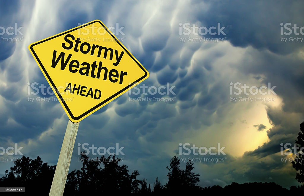 Stormy Weather Ahead Road Sign Against Dark Ominous Sky stock photo