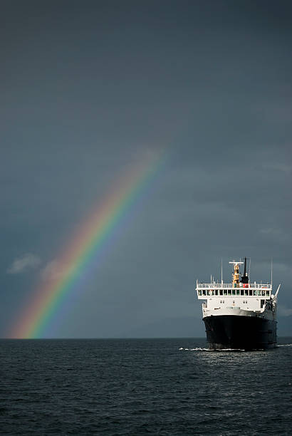 Stormy weather with ferry and rainbow stock photo
