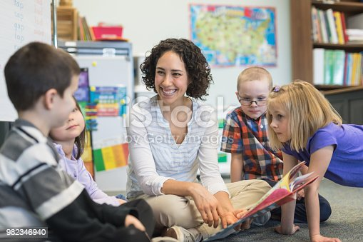 A young ethnic teacher reads a storybook to a group of first graders. They are gathered around her and listening intently as they sit on the floor.
