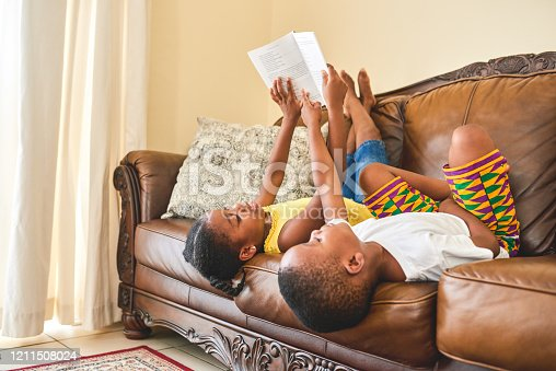 Shot of a little girl reading to her brother while lying on the couch at home