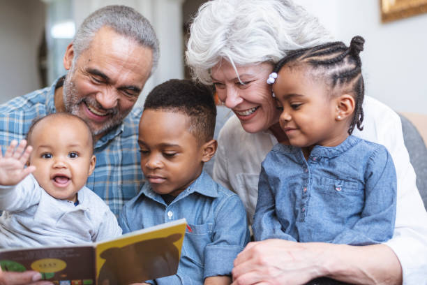 Story time with Grandma and Grandpa A retired senior couple support family by babysitting. Three young children sit on their grandparents' laps. The group is reading a book together. mixed race person stock pictures, royalty-free photos & images