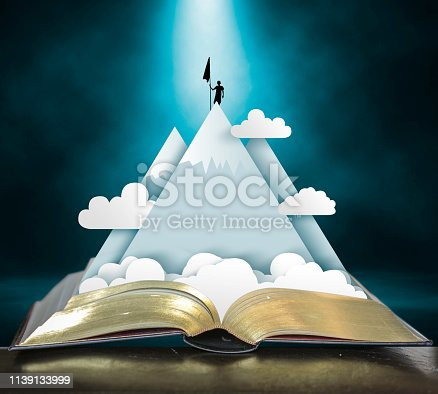 Open storybook with pop up of mountains, clouds and climber claiming the peak