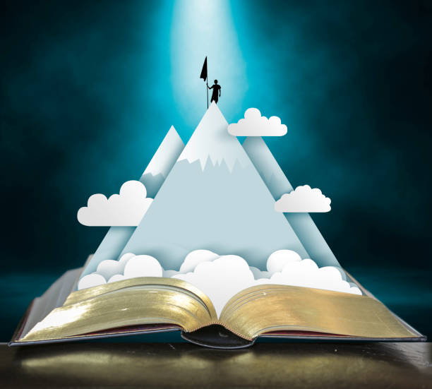 Storybook Open storybook with pop up of mountains, clouds and climber claiming the peak storytelling stock pictures, royalty-free photos & images