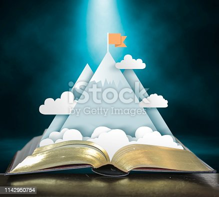 Open storybook with pop up of mountains, clouds, and climber claiming the peak