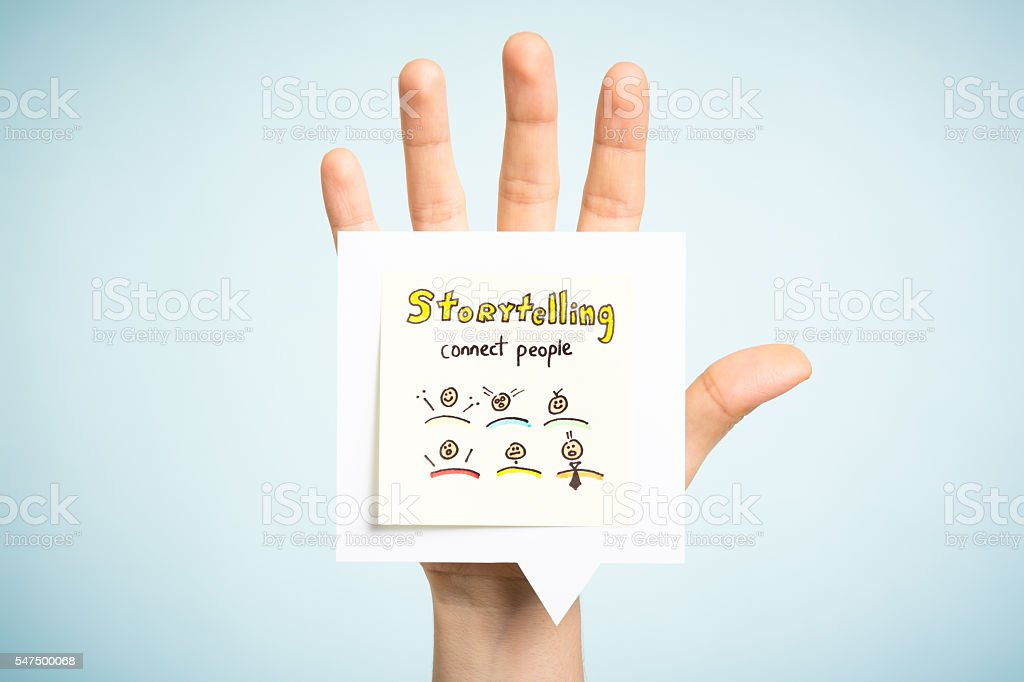 Storytelling concept. Hand up showing a paper note illustrated. stock photo