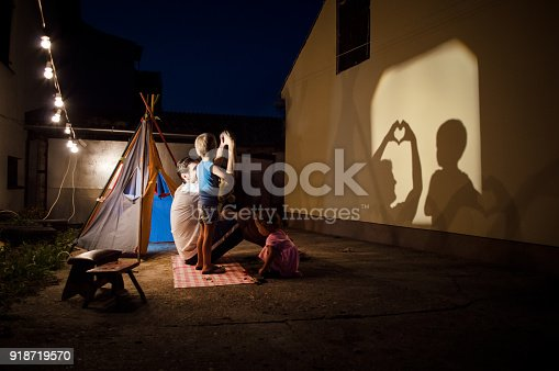 Father,brother and sister are playing with shadows in backyard of their home. There is tent, lights and good mood.