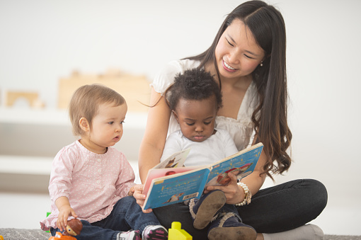 A woman reads a picture book to the babies on her lap.