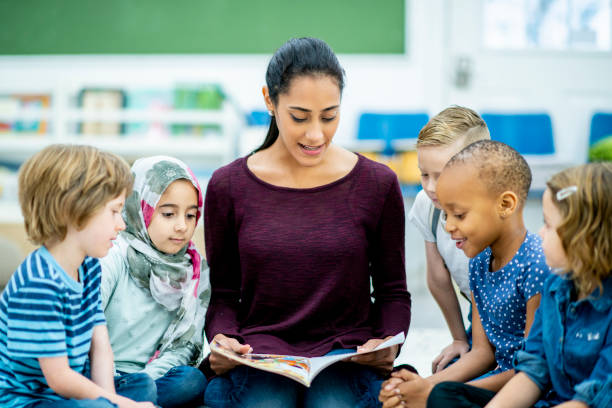 Storytime for preschoolers A diverse group of kids gathers around a female teacher of Middle Eastern descent and listens attentively to the story she is reading. preschool age stock pictures, royalty-free photos & images