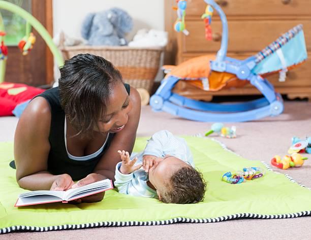Geschichtenerzählen am Playmat mit einer Pflegekraft reisen und Baby – Foto