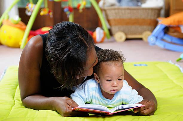 Geschichtenerzählen am Playmat mit Mutter und Baby – Foto