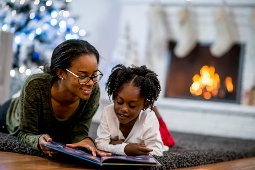 A mother and daughter of African descent are in indoors in their living room during Christmas time. They are wearing warm, comfortable clothes. They are laying on the carpet and reading a storybook together.