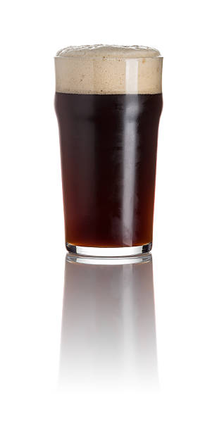 stout in a pint glass on a white background - dark beer stock photos and pictures