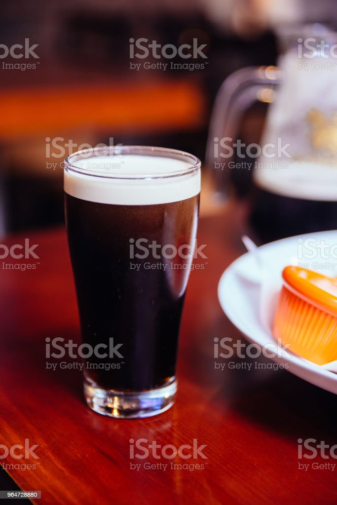 Stout (Black Beer) in glass on wooden table in the bar. royalty-free stock photo