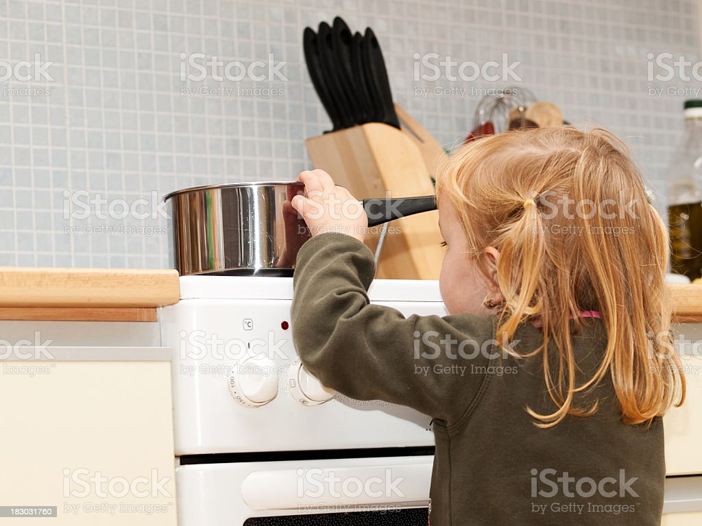 Stove danger in kitchen for a small child with blond hair stock photo