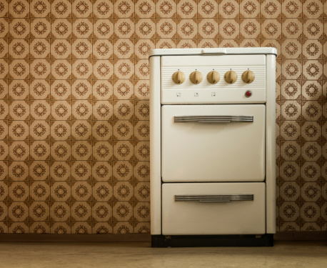 stove in old kitchen standing in front of pvc wallpaper