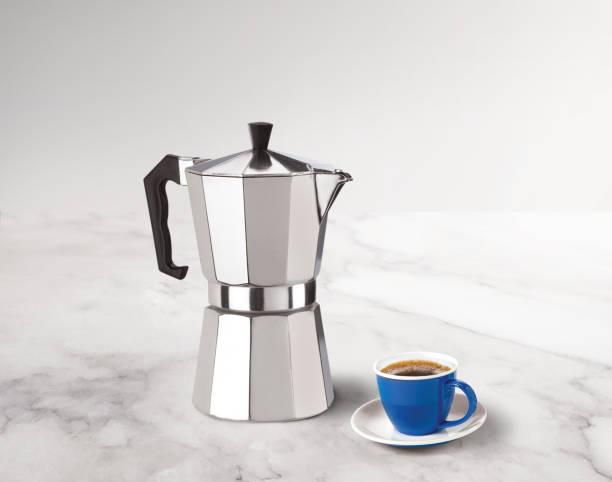 stovetop espresso maker with a coffee cup on a marble countertop - argento metallo caffettiera foto e immagini stock
