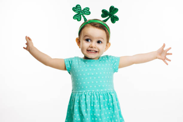 st.patrick's day clover head decoration on an excited toddler girl - carlos david stock pictures, royalty-free photos & images