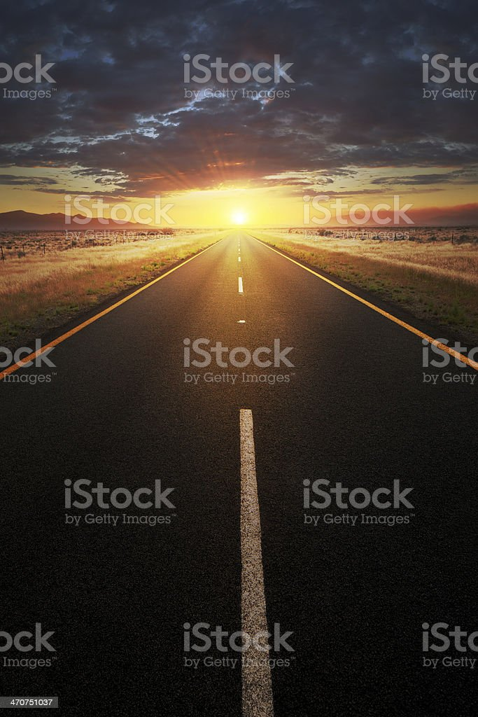 Straight asphalt road leading into sunlight stock photo
