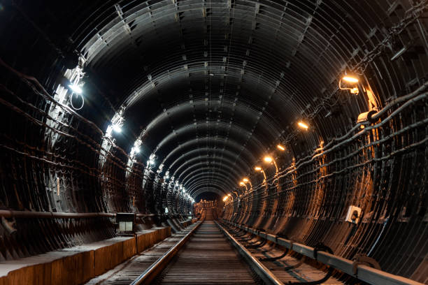 Straight circular subway tunnel with tubing and two different lights: white and yellow Straight circular subway tunnel with tubing and two different lights: white and yellow. underground stock pictures, royalty-free photos & images
