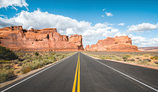 Straight highway road with yellow dividing lines seen in Arches National Park a beautiful sunny day.