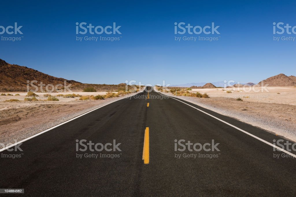 Straight, empty, two-lane road in the middle of the desert stock photo