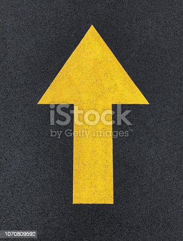 Straight arrow sign on asphalt