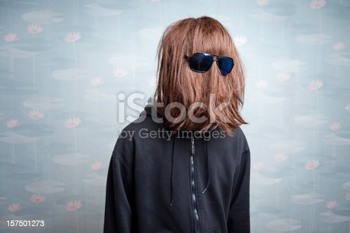 A man's long red hair hair completely cover his face with the exception of his glasses.  Vintage retro wallpaper in the background.  Horizontal with copy space.