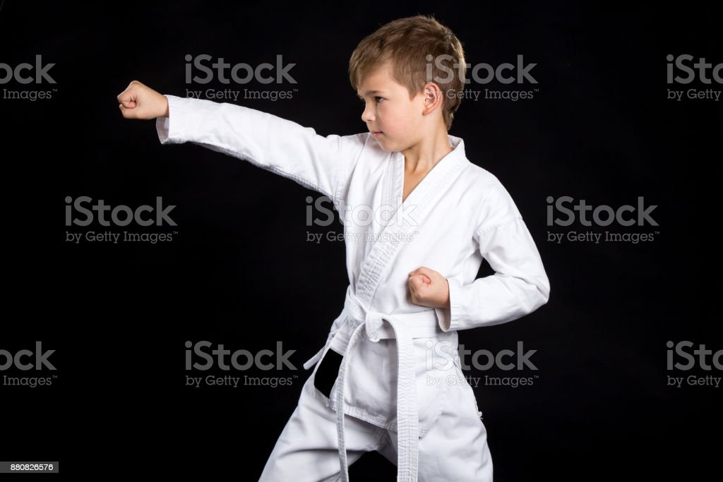 Straight karate arm hit. Kid in brand new kimono on isolated black background stock photo