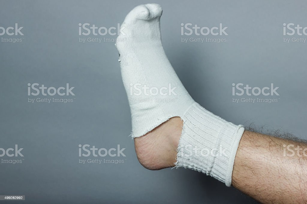 straight leg with a big hole in the sock stock photo